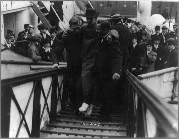 Harold Bridge, the assistant wireless operator on the Titanic suffered frostbitten feet. He is shown being carried from the Carpathia upon arrival in New York.